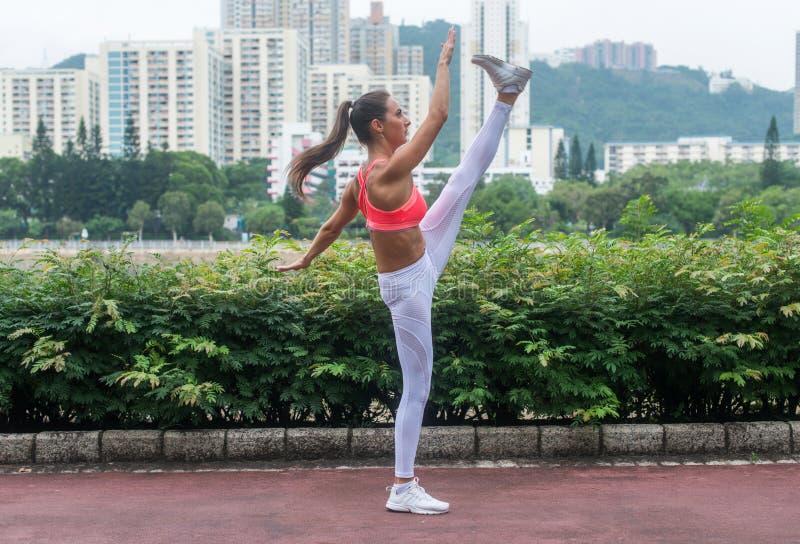 Konditionkvinnan som sträcker henne ben som gör kluven övning för yogaanseende i stad, parkerar utomhus i sommar royaltyfri fotografi
