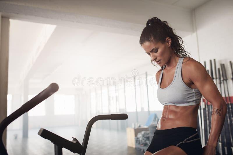 Konditionkvinnasammanträde på idrottshallcykeln royaltyfria bilder