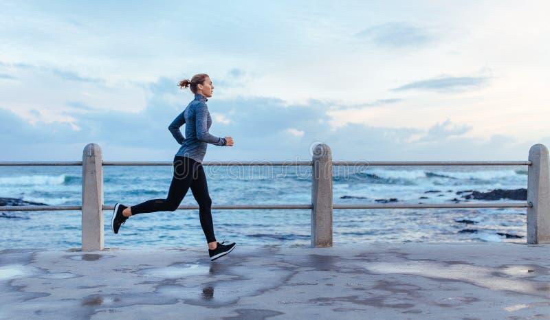 Konditionkvinnaspring på en väg vid havet arkivfoton
