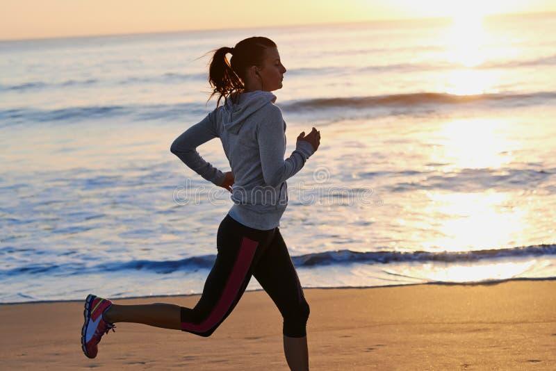 Konditionkvinnaspring på strand arkivfoto