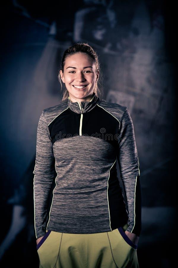 Konditionkvinnastående på idrottshallen Le den lyckliga kvinnliga konditioninstruktören som ser kameran arkivfoto