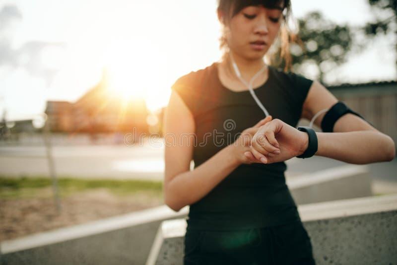 Konditionkvinnlig som kontrollerar hennes kapacitet på smartwatch fotografering för bildbyråer