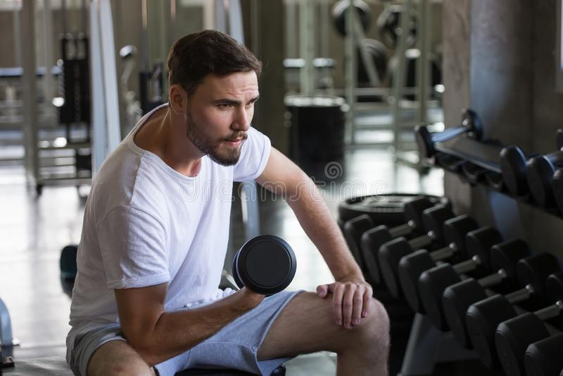 konditionman som gör övningar som sitter med hantlar för lyfta för vikt i idrottshall ung manlig utbildning för sport utarbeta su fotografering för bildbyråer