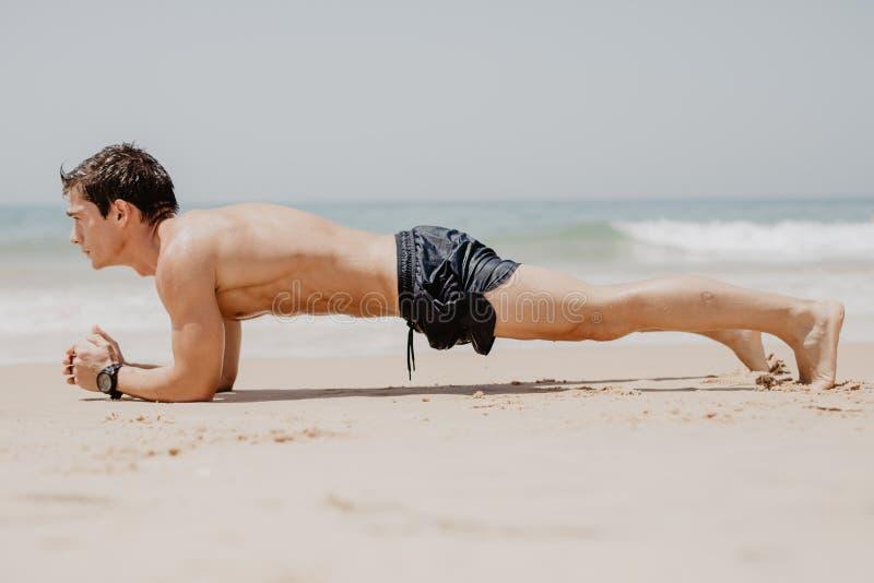 Konditionman som gör liggande armhävningövning på stranden Ståenden av passformgrabben som utarbetar hans armmuskel- och kroppkär arkivfoton