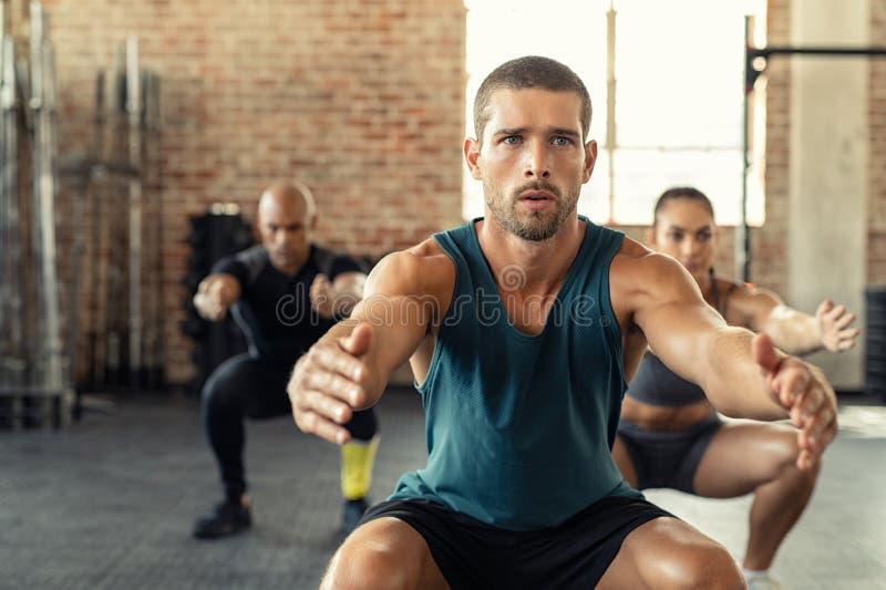 Konditionman som squatting med grupp på idrottshallen arkivbild