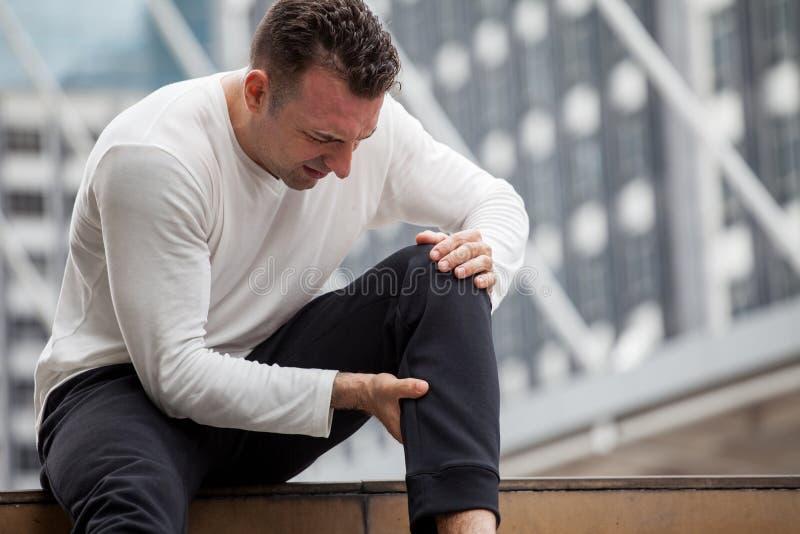 konditionmannen har knäet att smärta att sitta på moment av trappan i staden sportskadaben av inkört stads-, olycka, övning, geno royaltyfri fotografi