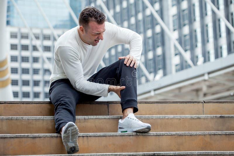 konditionmannen har kn?et att sm?rta att sitta p? moment av trappan i staden sportskadaben av ink?rt stads-, olycka, ?vning, geno royaltyfria bilder