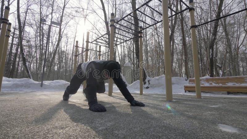 Konditionmannen som att göra skjuter, ups, och sträcka övar på utbildning för vintersportar royaltyfria bilder