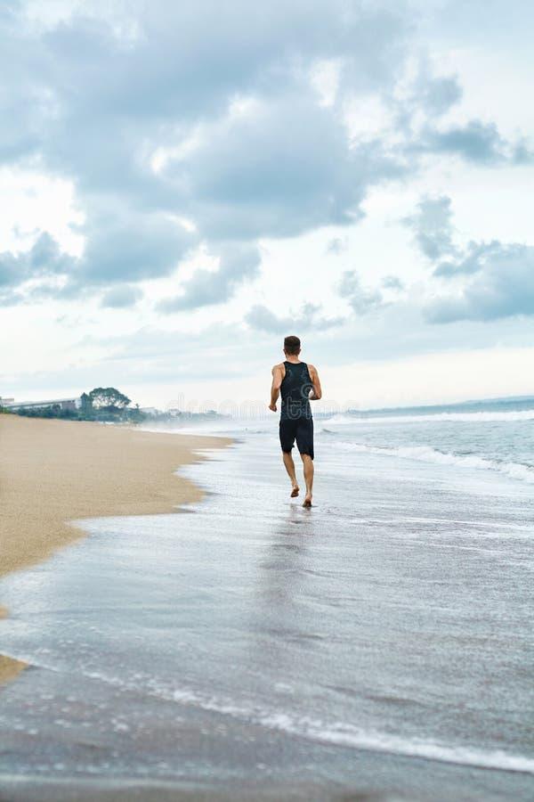 Konditionmanspring på stranden Löpare som joggar under utomhus- genomkörare royaltyfri bild