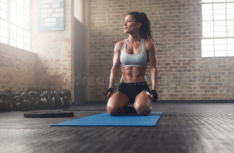Konditionmodell i sportswear på den matta övningen royaltyfri foto