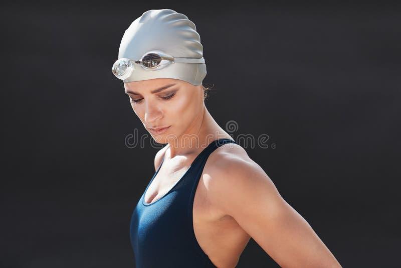 Konditionmodell i swimwear över svart bakgrund royaltyfria bilder