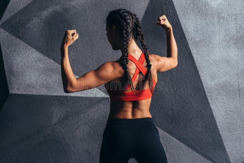 Konditionmodell som poserar visningmuskler av baksidan och bicepens arkivfoton
