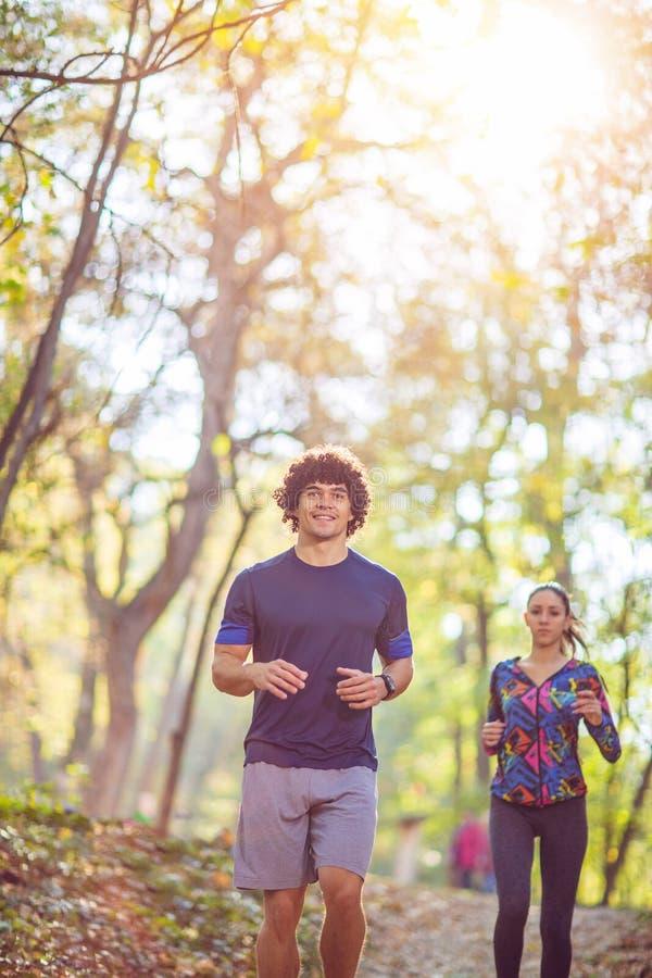 Konditionpar som utomhus joggar och kör i natur sunt l royaltyfri bild
