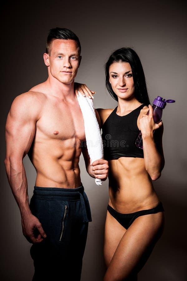 Konditionparet poserar i studio - den färdiga mannen och kvinnan arkivfoton