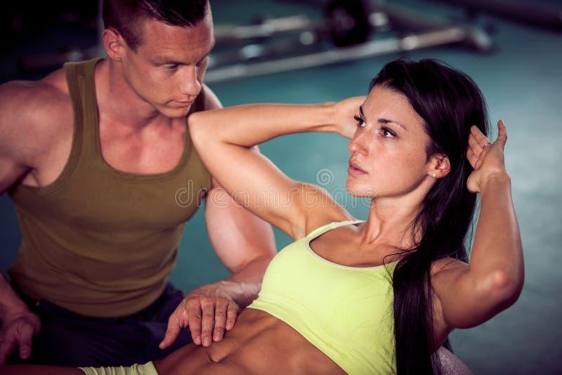 Konditionpargenomkörare - den färdiga mannen och kvinnan utbildar i idrottshall royaltyfria bilder