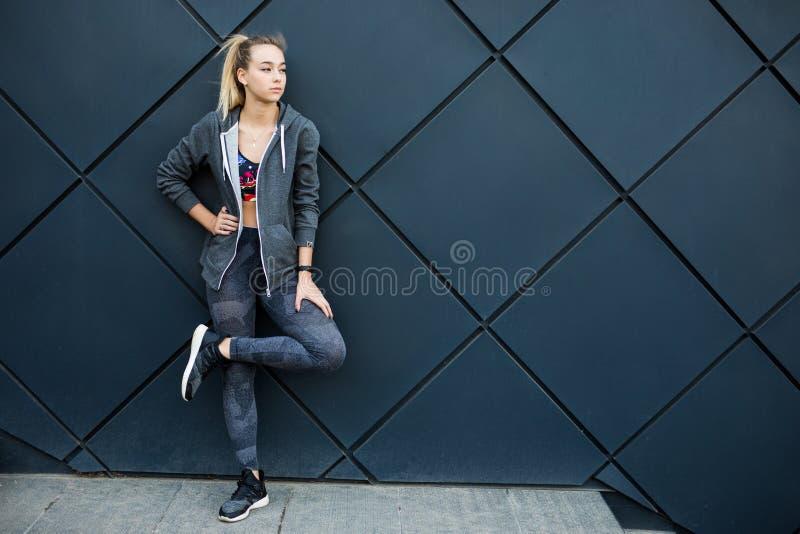 Konditionsportflicka i modesportswearen som gör konditionövningen i gatan, utomhus- sportar, stads- stil arkivbild