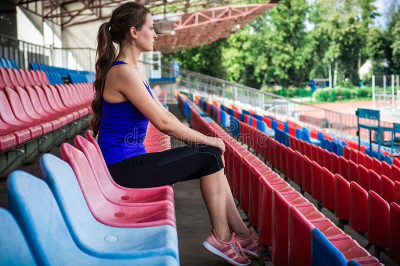 Konditionsportflicka i modesportswearen som gör yogakonditionövningen i gatan, utomhus- sportar, stads- stil arkivfoto