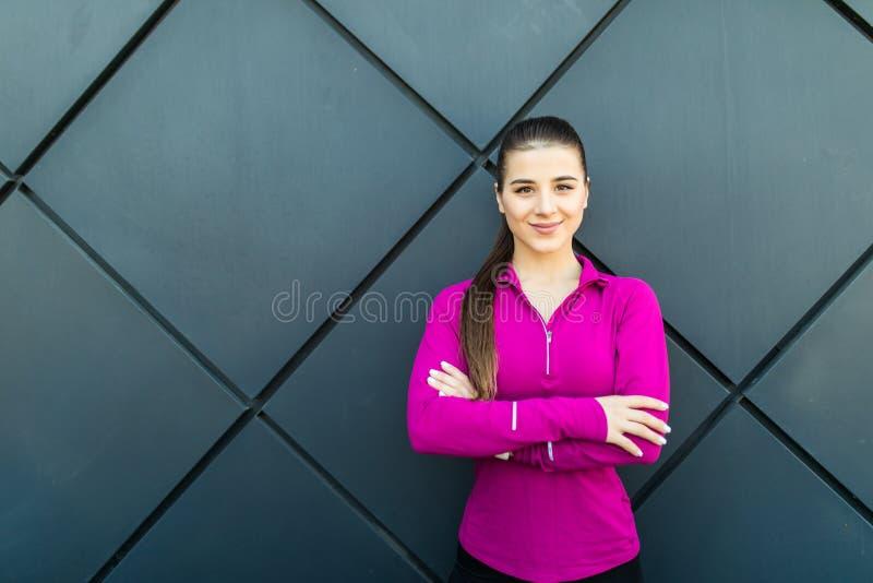 Konditionsportflicka i sportswearen som gör konditionövningen i gatan, utomhus- sportar, stads- stil arkivbilder