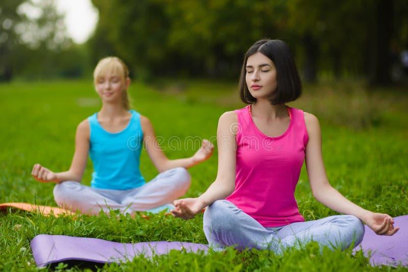Konditionsportflickor i sportswearen som gör yogakondition, övar utomhus- royaltyfria bilder