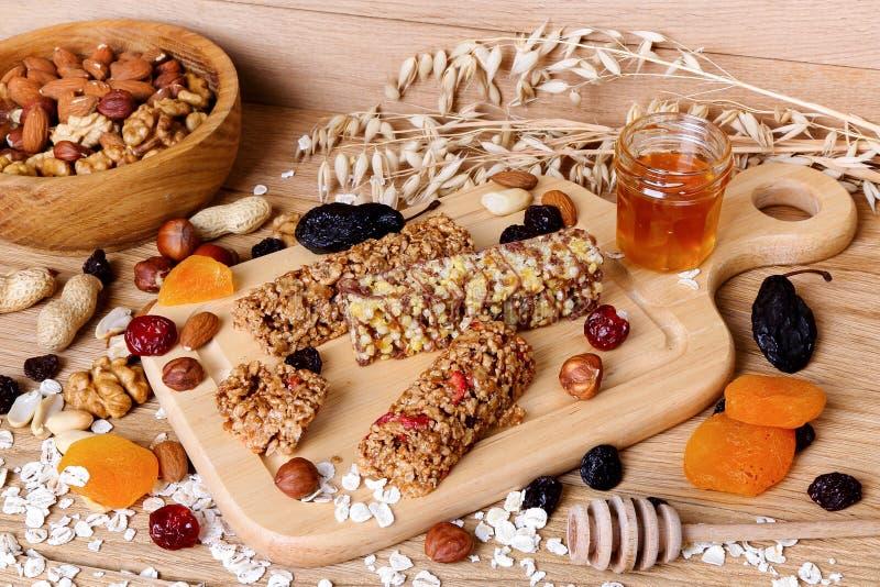 Konditionstänger med granola, havremjölet, muttrar, torkade - frukt och honung arkivfoto