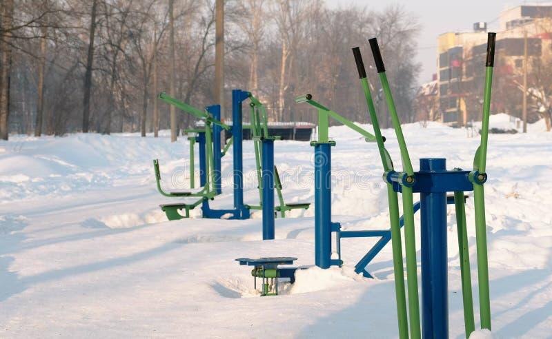Konditionutrustning för sportar som täckas med insnöat vinterstaden, parkerar fotografering för bildbyråer