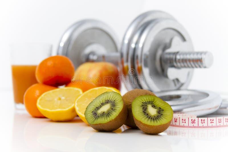 Konditionutrustning och sund mat, äpple, nektariner, kiwi, lem royaltyfri bild