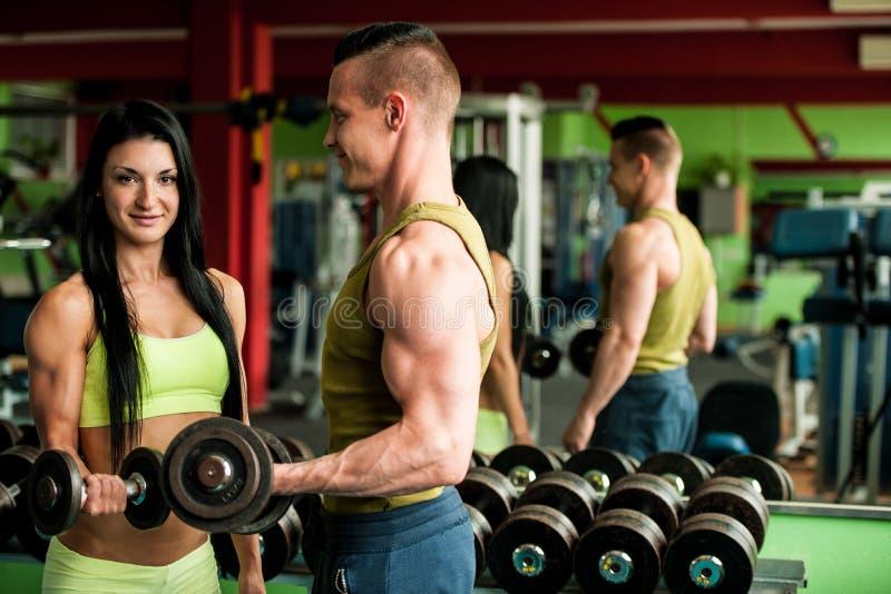 Konditionyouplegenomkörare - färdiga mann och kvinnan utbildar i idrottshall fotografering för bildbyråer