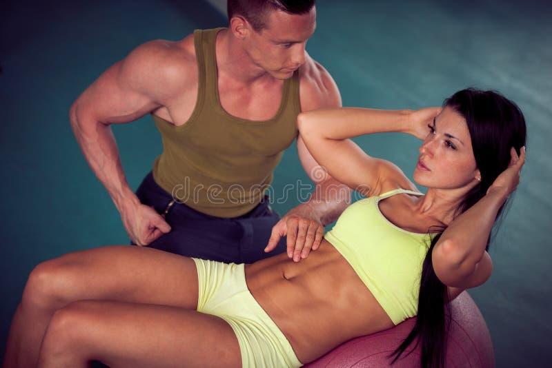 Konditionyouplegenomkörare - färdiga mann och kvinnan utbildar i idrottshall royaltyfria foton