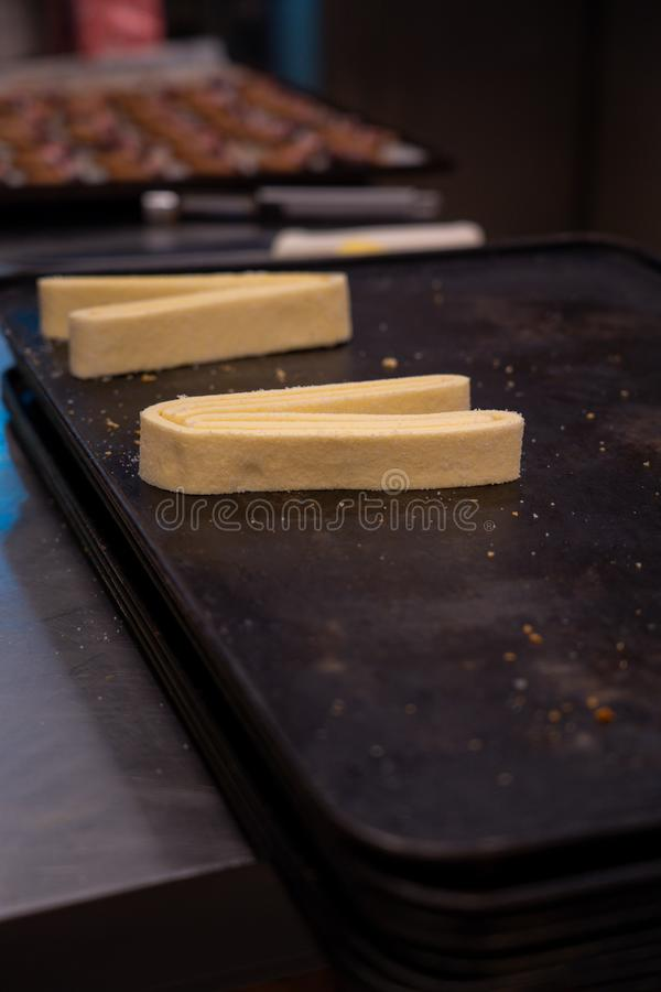 Konditor bearbeitet den Blätterteigteig, Handwerker, der Feinschmecker, vorbereitet gebacken zu werden lizenzfreie stockfotografie