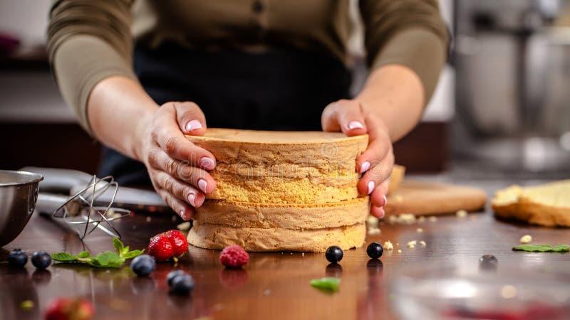 Konditor förbereder en ljusbrun kaka i hem- kök eller i en restaurang Begreppet av processen av att göra cakeÑ‹, royaltyfri fotografi
