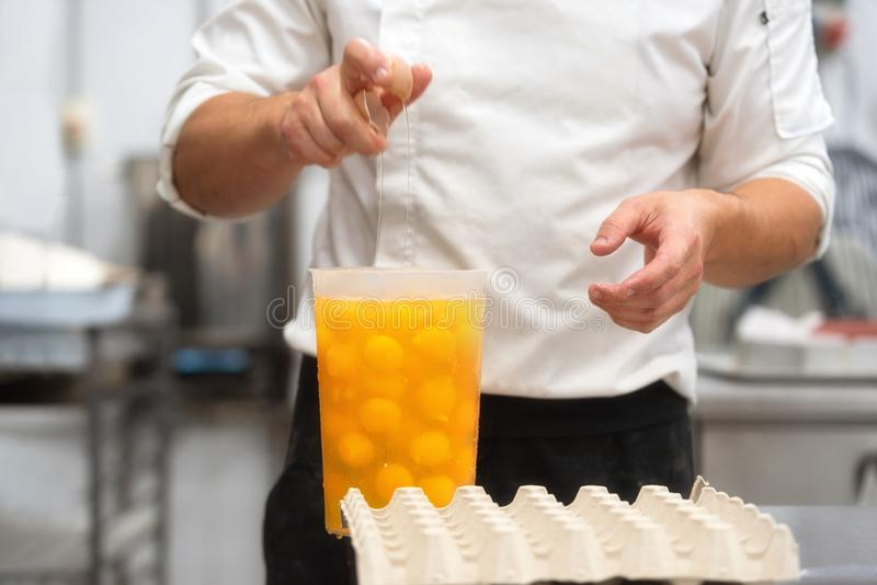 Konditor som bryter ägg för att förbereda kakan royaltyfri foto