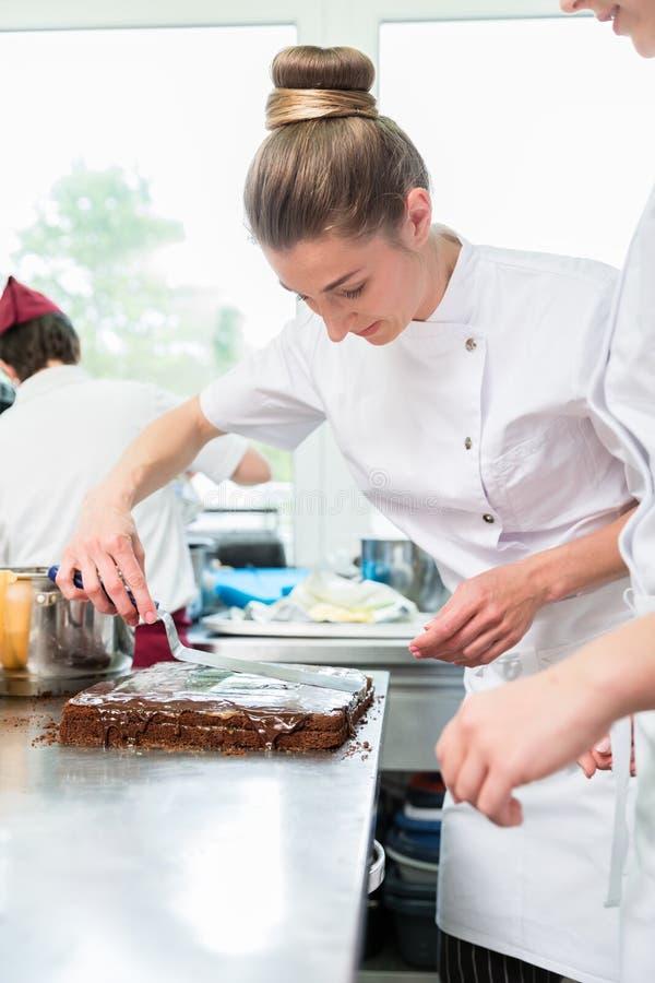 Konditor som sätter choklad som glasyr på kaka på kakan arkivbilder