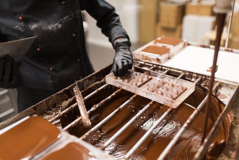 Konditor som tar bort överskott choklad från form royaltyfri foto