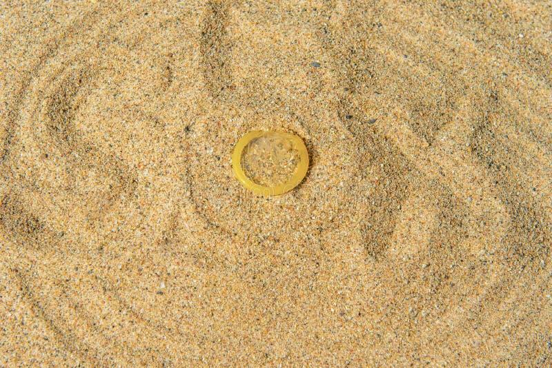 Kondom na żółtym piasku, tło zdjęcie royalty free