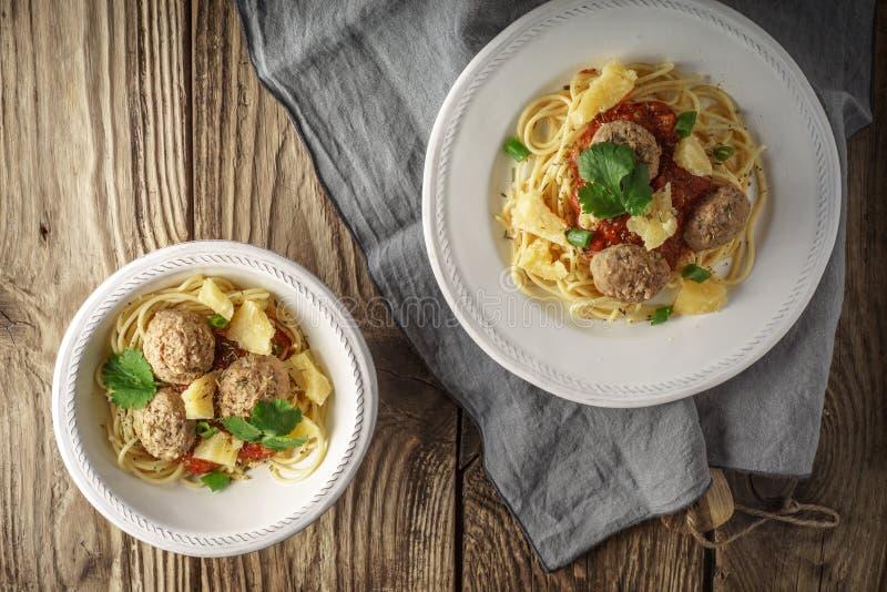 Konfektions- spagetti med köttbullar på den gamla tabellen arkivfoto