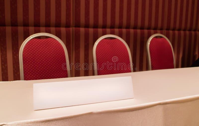 Konferenstabellen med röda stolar och triangeln stiger ombord i mötesrum royaltyfri fotografi