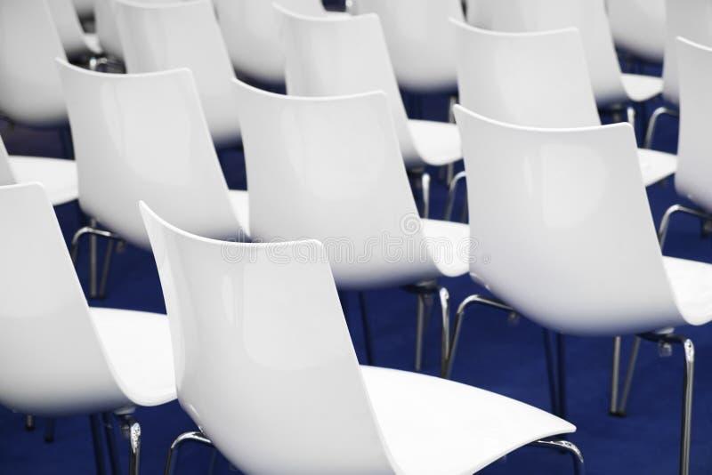 Konferenzstühle im Geschäftsraum, Reihen von weißen bequemen Plastiksitzen im leeren Unternehmensdarstellungssitzungsbüro, Detail stockfoto