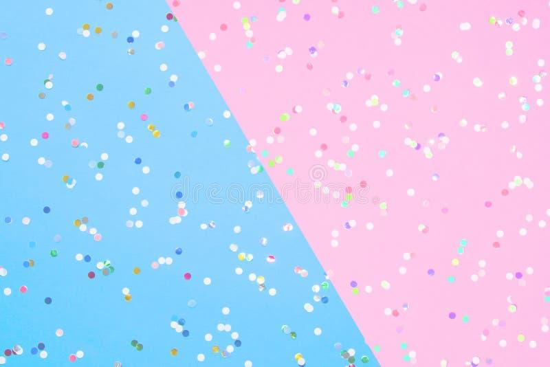 Konfettier spridda på blått och rosa papper arkivfoton