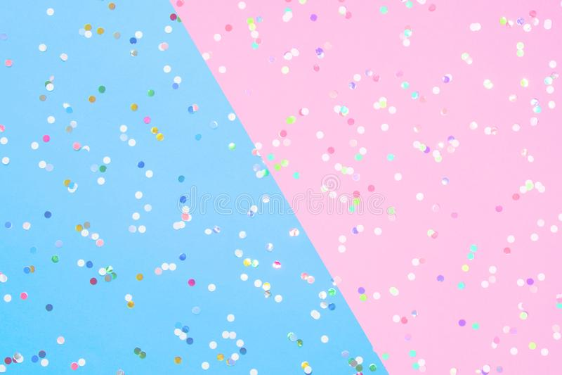 Konfettis zerstreut auf blaues und rosa Papier stockfotos