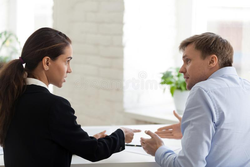 Konflikt des weiblichen Chefs und des männlichen Büroangestellten stockfotografie