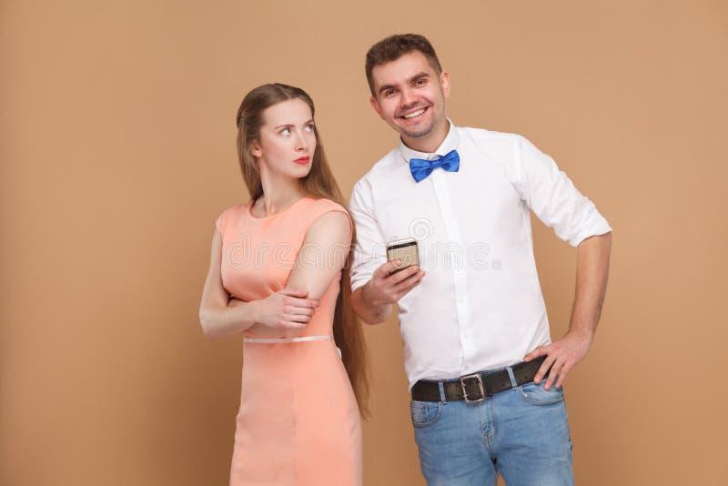 Konflikt Glückliche Mannstellung, Holdinghandy und schauen a stockfotos