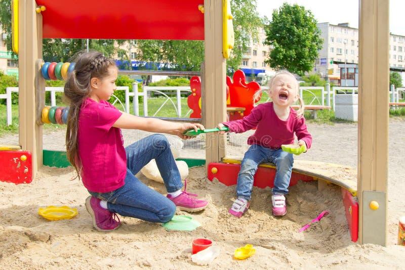 Konflikt på lekplatsen Två systrar som slåss över en leksakskyffel i sandlådan arkivfoton