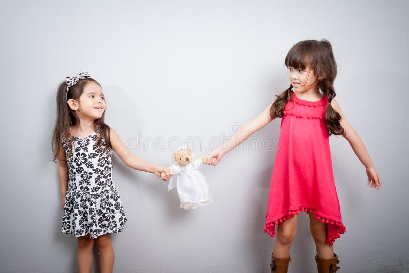 Konflikten mellan två systrar ungarna slåss, kampen över för leksak royaltyfri bild