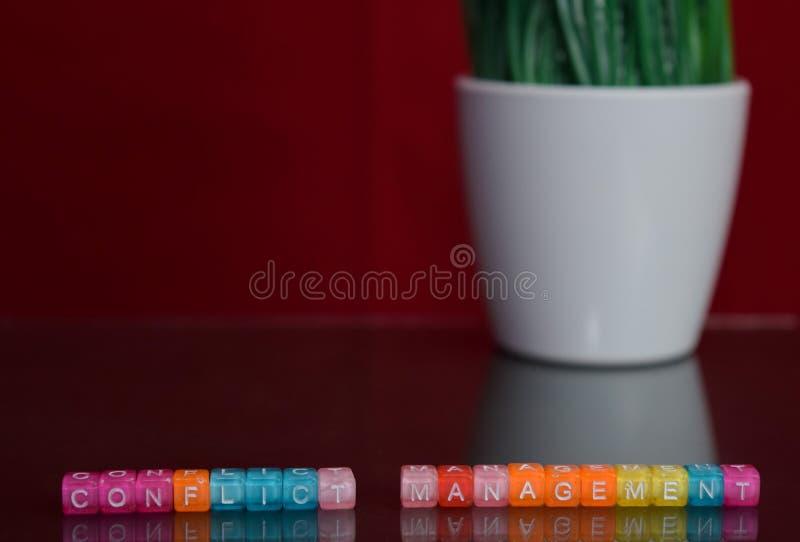 Konfliktmanagementtext am bunten Holzklotz auf rotem Hintergrund Schreibtischbüro und Ausbildungskonzept stockfotos