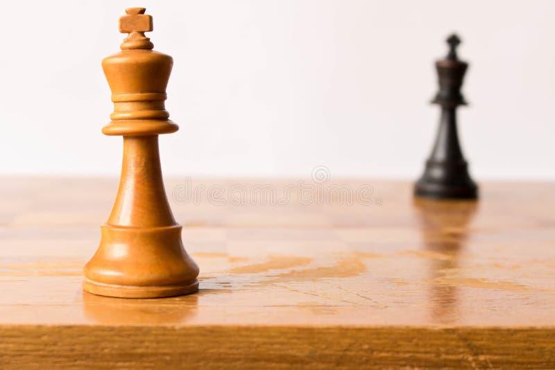 Konfrontacja między białym i czarnym szachowym królewiątkiem Szachowa gra zdjęcie stock