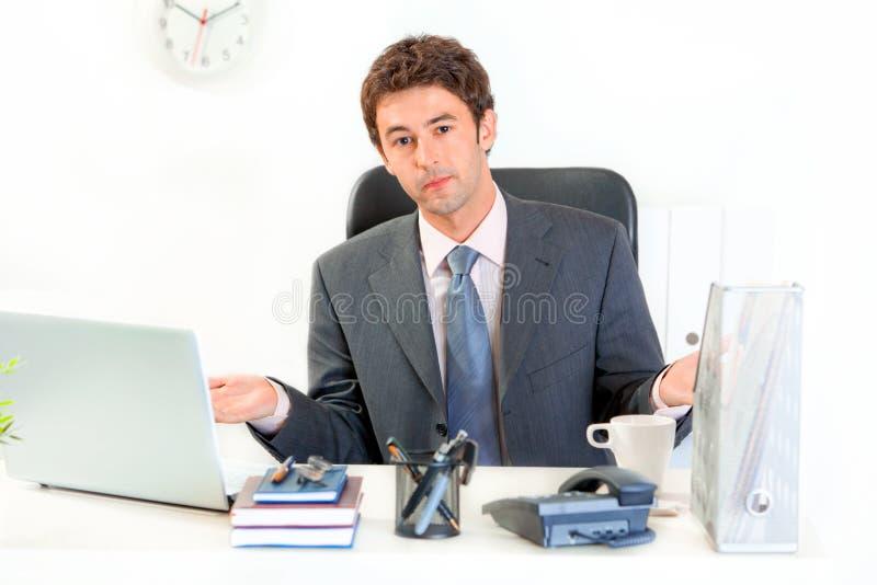 Konfuser Geschäftsmann, der am Büroschreibtisch sitzt lizenzfreie stockfotografie