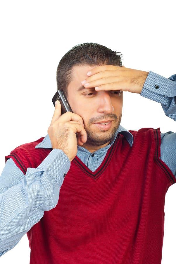 Konfuser Mann, der durch Telefonmobile spricht lizenzfreie stockfotografie