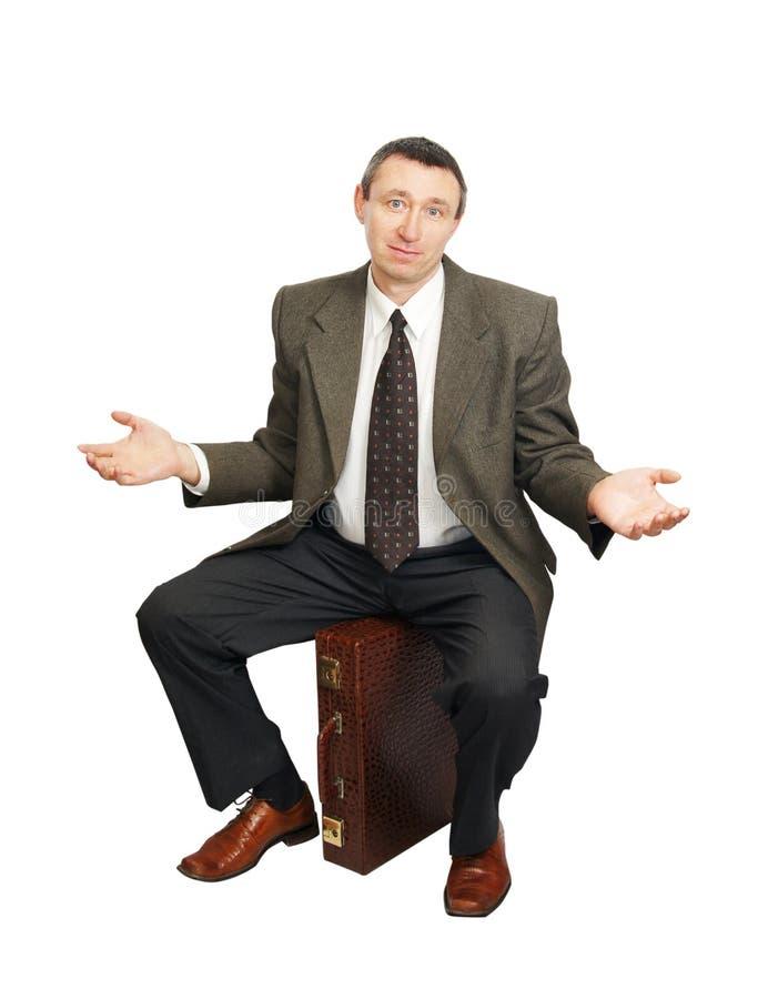 Konfuser Mann sitzt auf Koffer stockbilder