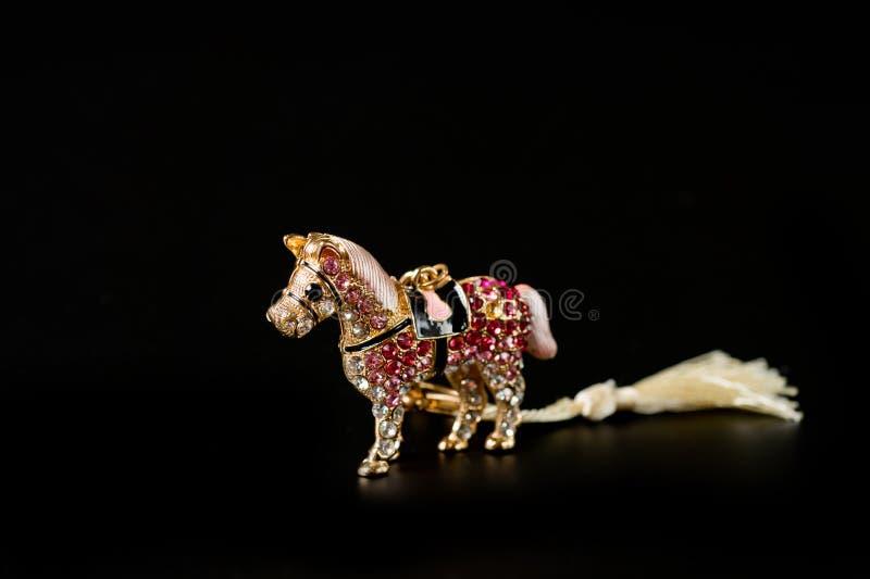 Konia figurka pamiątka pamiątka łańcuch w złotym kolorze lub z jasnymi kamykami kulonymi na ciemnym tle zdjęcia royalty free