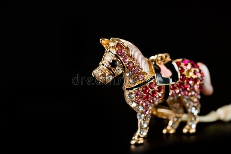 Konia figurka pamiątka pamiątka łańcuch w złotym kolorze lub z jasnymi kamykami kulonymi na ciemnym tle obraz stock